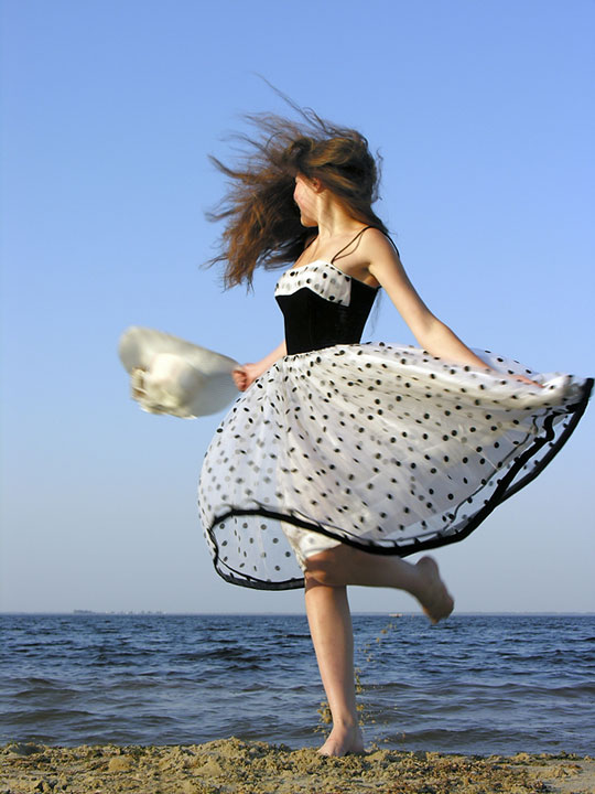 woman wearing a dress on a windswept beach